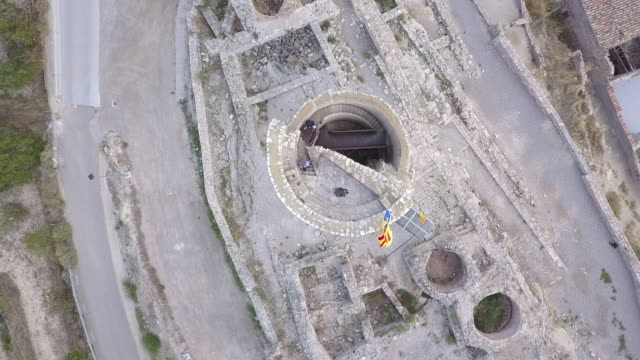 People climb up medieval tower in Catalonia, overhead aerial