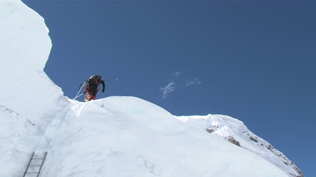 stockvideo's en b-roll-footage met ms people climbing and walking to ladder on ice / mt. everest, nepal - mount everest