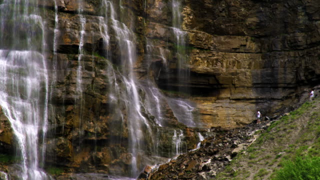 people climbing around the base of bridal veil falls in provo, utah. - provo stock-videos und b-roll-filmmaterial