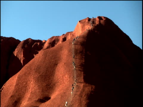People climbing up Uluru Australia
