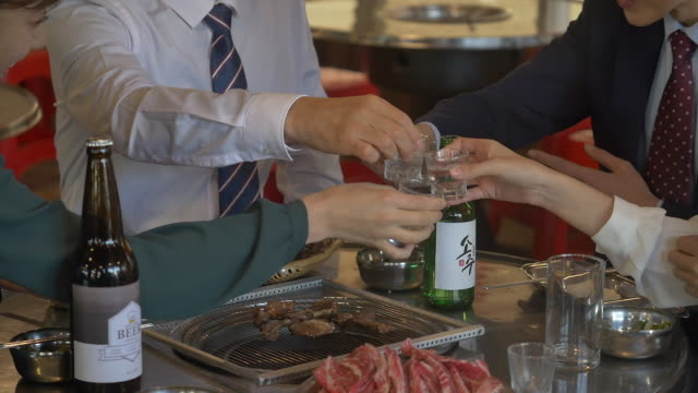 people clinking soju glasses at a company get-together - giacca e cravatta video stock e b–roll