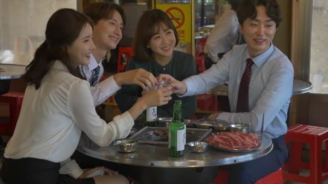 people clinking soju (korean alcohol) glasses at a company get-together - skjorta och slips bildbanksvideor och videomaterial från bakom kulisserna