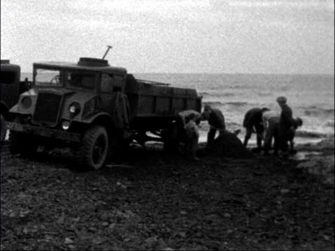 people collect sea coal from the beach in county durham; england: county durham: ext waves lapping on beach shovels shovelling coal from the shallows... - county durham england stock videos & royalty-free footage