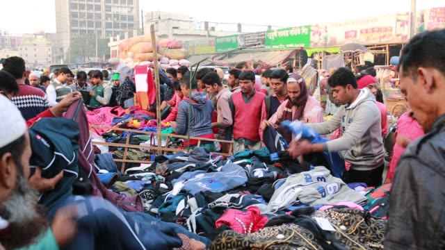 People collect warm cloth from a street market during cold wave in Dhaka Bangladesh on January 08 2018 The cold wave continues to disrupt life across...
