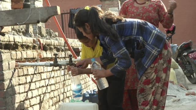 stockvideo's en b-roll-footage met people collect water at an idp camp in bhaktapur / a major earthquake hit kathmandu mid-day on saturday, april 25th, and was followed by multiple... - opluchting