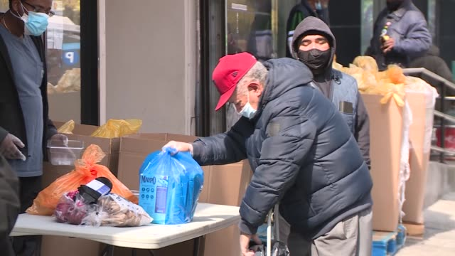 vídeos de stock e filmes b-roll de people collecting meals in new york as the city struggles with unemployment and access to food because of the coronavirus pandemic - desemprego