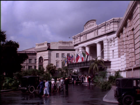 vídeos de stock, filmes e b-roll de people come and go in front of the raffles hotel in singapore. - 1942