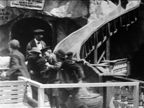 b/w 1903 people coming down slide in amusement park ride / coney island - coney island brooklyn stock videos & royalty-free footage