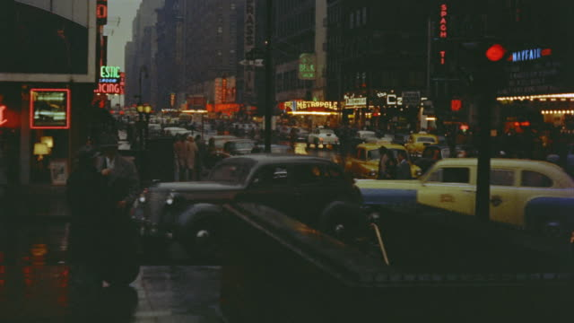 1953 ws people coming out of subway entrance near times square on rainy night / manhattan, new york - 1950点の映像素材/bロール