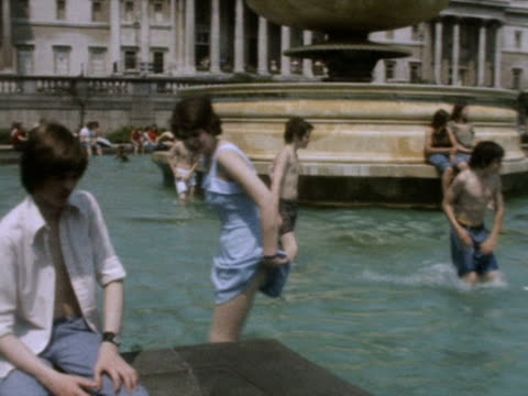 vídeos de stock, filmes e b-roll de people cool off in the trafalgar square fountains during the heatwave of 1976 - 1976