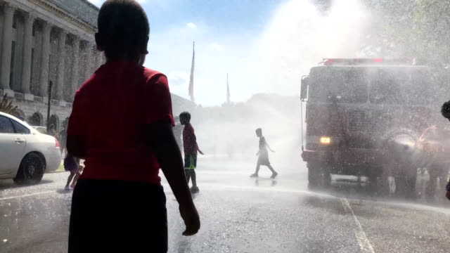 people cool themselves in water spray from a fire truck outside the annual smithsonian folklife festival on independence day july 4 2018 in... - 熱波点の映像素材/bロール