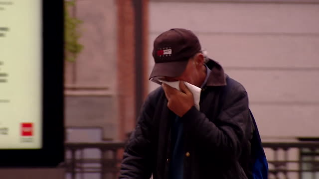 people cover their mouths as they practise social distancing in madrid during coronavirus outbreak - spanien stock-videos und b-roll-filmmaterial