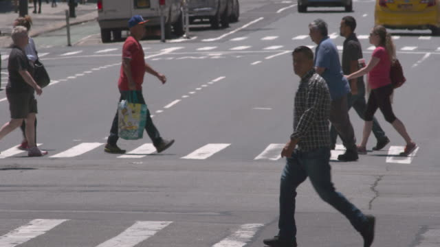 People cross a busy intersection in New York City in slow motion on a summer day.