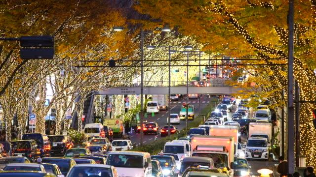people cross and cars go through among the illuminated tree lined omotesando street for winter holydays season while the dusk at jingumae, shibuya tokyo japan on december 06 2017. - treelined stock videos & royalty-free footage