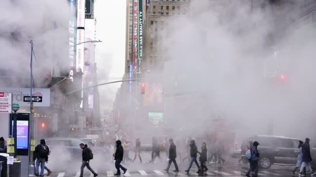 people cross and traffic goes through the avenue under the drifting steam among the midtown manhattan buildings in the snow day around the times square in midtown manhattan new york city ny usa on jan. 18 2020. - traffic jam stock videos & royalty-free footage