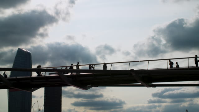 People cross Millennium Bridge silhouetted against dramatic clouds