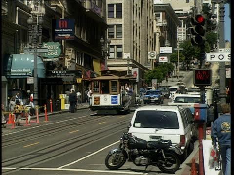 People cross road at pedestrian crossing as traffic follows tram down street