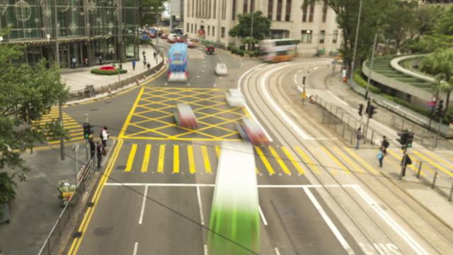 vidéos et rushes de personnes traversent la rue et la circulation - île de hong kong