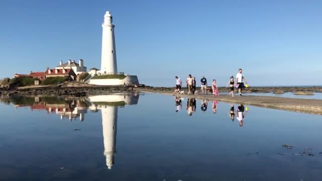 people cross the causeway from st mary's lighthouse island northumberland as the tide comes in - causeway stock videos & royalty-free footage