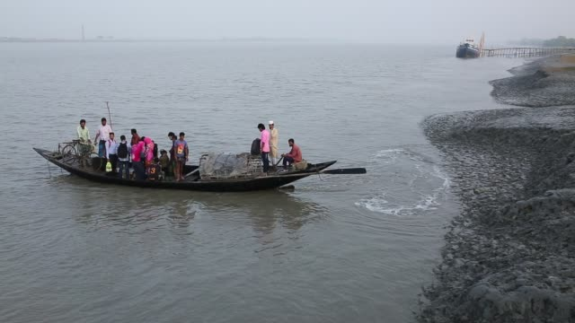 vidéos et rushes de people cross the river by boat in a rural coastal area in bangladesh - terre en vue