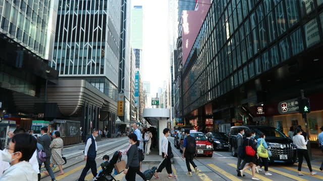 vídeos de stock, filmes e b-roll de people cross the road in a financial district of hong kong on november 12 2020. wearing mask is mandatory at outdoor except when doing exercises in... - higiene