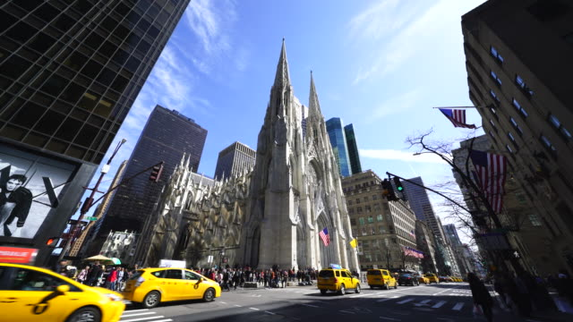 people cross the street and cars go through fifth avenue at intersection of the st. patrick's cathedral among the midtown manhattan skyscrapers at new york ny usa on apr. 21 - st. patrick's cathedral manhattan stock videos and b-roll footage