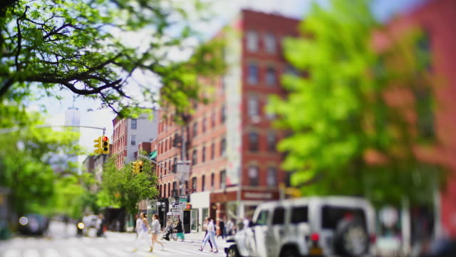 vídeos de stock e filmes b-roll de people cross the street and cars run on the avenue among the soho buildings, which are surrounded by fresh green trees at new york city ny usa on may 16 2019. - apartamento tipo loft