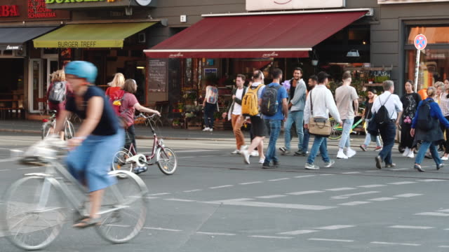 people cross the street and some people ride bicycles in berlin, germany - pedestrian stock videos & royalty-free footage