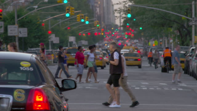 People cross the street during Rush hour traffic on a busy 8th Avenue early evening.  Cars, and cabs rush by.