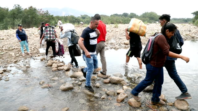 people cross through the low waters of the táchira river near the simón bolívar international bridge which connects cúcuta with the venezuelan town... - 通行止め点の映像素材/bロール