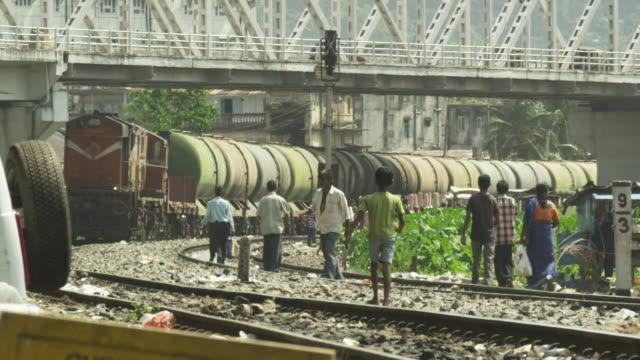 People cross train lines in Guwahati in Assam, India.