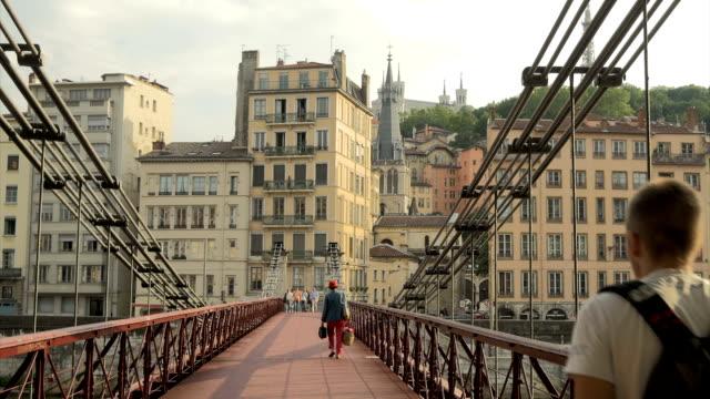 people crossiing bridge over river saone,ms pan - 尖り屋根点の映像素材/bロール
