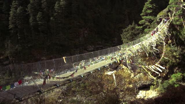 vídeos de stock e filmes b-roll de people crossing a bridge over a gorge in nepal. - ponte suspensa