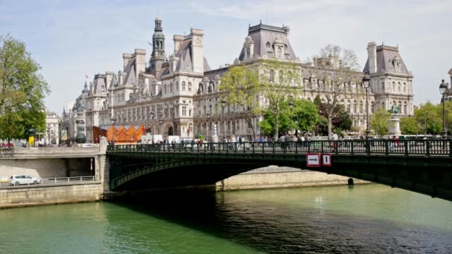 people crossing a bridge over the seine river in paris, france - town hall stock videos & royalty-free footage