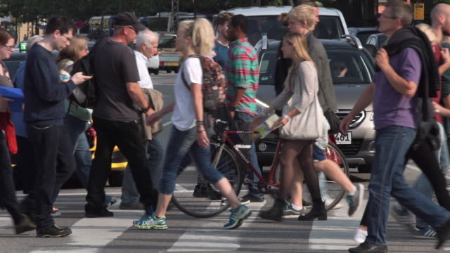 people crossing a street in copenhagen as traffic waits - denmark stock videos & royalty-free footage