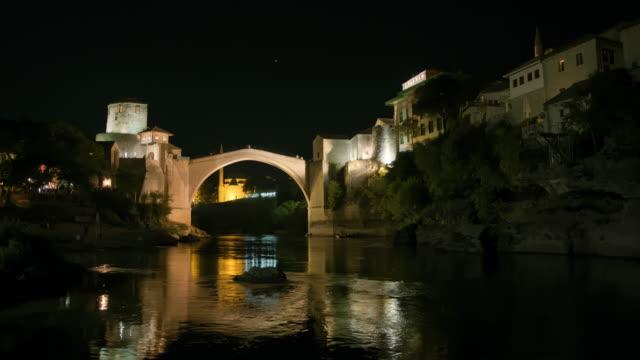 wa 人在夜間穿越莫斯塔爾的一座舊橋 - 波斯尼亞 赫塞哥維納 個影片檔及 b 捲影像