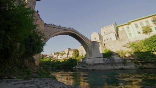 在莫斯塔爾,洛杉磯人越過內雷特瓦河上的一座老橋 - 波斯尼亞 赫塞哥維納 個影片檔及 b 捲影像