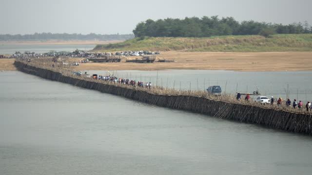 people crossing bamboo bridge by car, motorbike and a small boat crossing under - 干潮点の映像素材/bロール