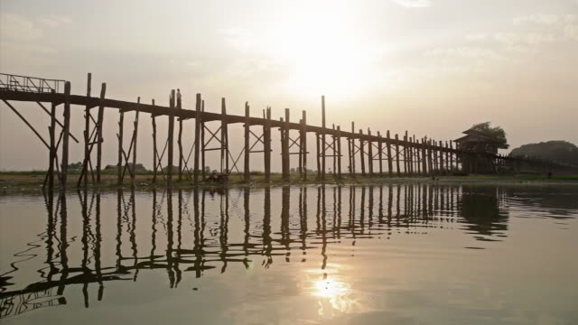 ws pan people crossing  bridge and  sun is reflecting on the water  / mandalay, mandalay division, myanmar - mandalay stock videos and b-roll footage