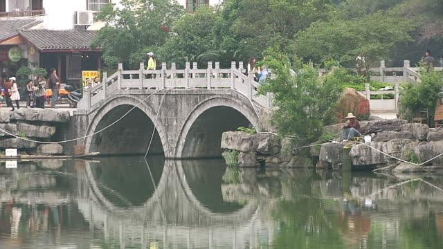 ws people crossing bridge over lake / close to li river, guangxi, china - li river stock videos & royalty-free footage