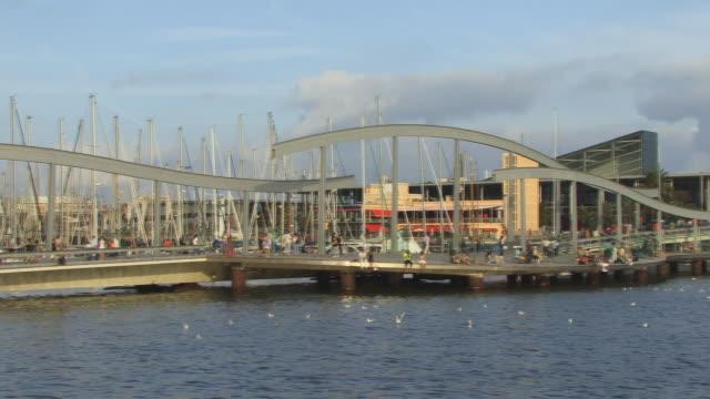 vídeos de stock e filmes b-roll de ws, pan, people crossing footbridge connecting port vell and maremagnum, barcelona, spain - porto de barcelona