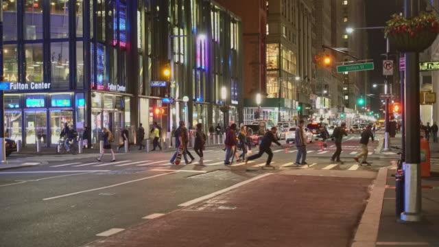 夜のワンワールドトレードセンターの近くにフルトンストリートを横断する人々。 - 歩道点の映像素材/bロール