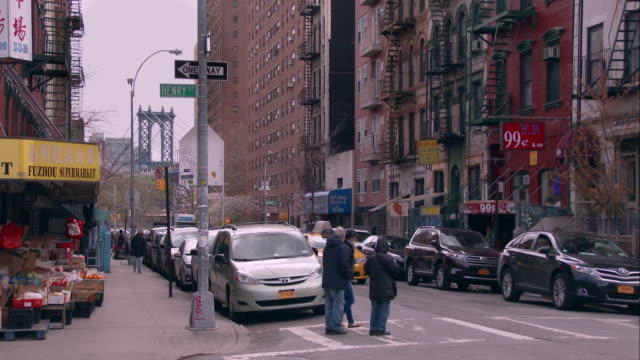 people crossing henry street in chinatown with the manhattan bridge in the background - ecke eines objekts stock-videos und b-roll-filmmaterial