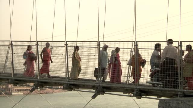 vídeos de stock, filmes e b-roll de people crossing lakshman jhula bridge - rishikesh
