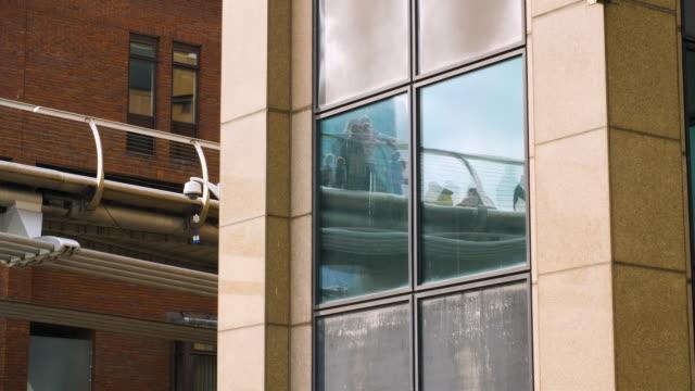 vídeos y material grabado en eventos de stock de people crossing millennium bridge are reflected in the exterior windows of an office building - puente del milenio londres