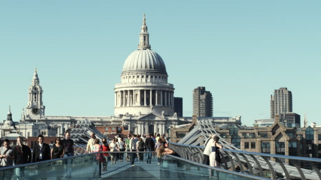 ws people crossing millennium bridge, st paul's cathedral in background / london, united kingdom - rosso stock videos & royalty-free footage