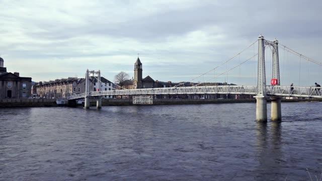 People crossing Ness River using Greig Street suspension foot bridge, Inverness, Scotland