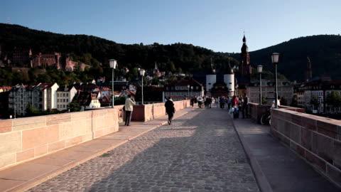 ws people crossing old bridge, bridge gate and church of the holy spirit in background / heidelberg, baden-wuerttemberg, germany - pedestrian zone stock videos & royalty-free footage