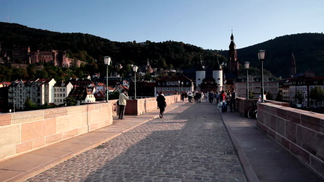 ws people crossing old bridge, bridge gate and church of the holy spirit in background / heidelberg, baden-wuerttemberg, germany - baden württemberg stock videos & royalty-free footage