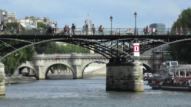 ms people crossing pont des arts, pont neuf and pont au change in background, paris, france - ポンヌフ点の映像素材/bロール